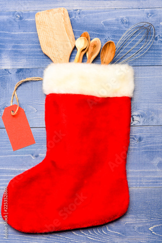 Kitchenware as wooden spoons lay in Christmas sock with tag