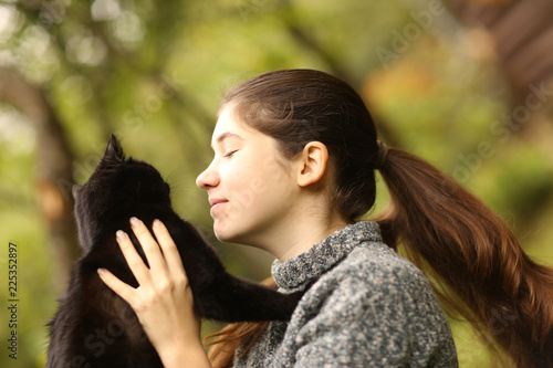 Cuadros en Lienzo summer sunny photo of teenager girl hug cuddle cat close up outdoor photo