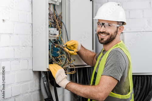 фотография smiling handsome electrician repairing electrical box with pliers in corridor an