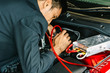 This career inspection asian man car service charging battery car on