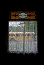 Interior Of A Room In An Old House, Looking Out Through A Window With White Lace Curtains, And A Small, Beautiful Stained Glass Panel Above. Outside Is A White Porch Railing And A Yellow School Bus.