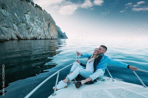 Young Couple Relaxing on a Yacht. Happy wealthy man and a woman by private boat have sea trip.