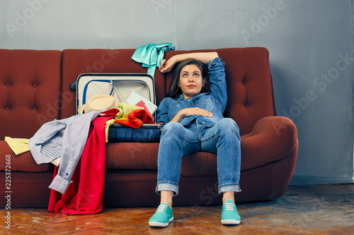 Tired woman lying on sofa with travel suitcase.