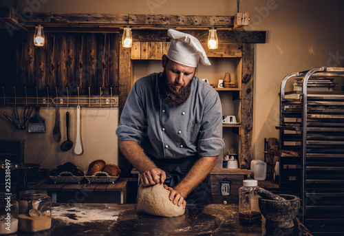 Concentrated chef kneading dough in the kitchen. Fototapete