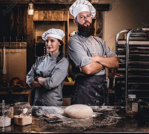 Fotografia Chef with his assistant in cook uniform posing with crossed arms near table with ready dough in the bakery