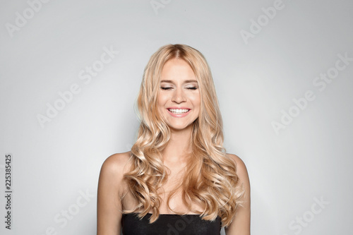 Beautiful woman with healthy long blonde hair on light background Tablou Canvas