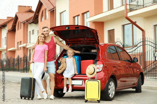 Happy family near car trunk with suitcases outdoors