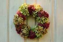 A Charming Vintage-style Wreath Of Hydrangea Flowers And A Prominent Stonecrop Is A Wonderful Decoration Of The White Door To The House.
