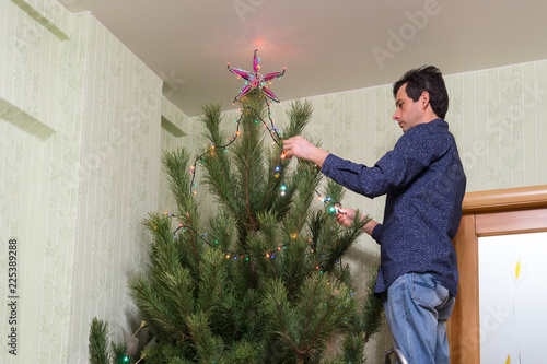 Fotografia  Handsome middle-aged man decorates a Christmas tree with a star