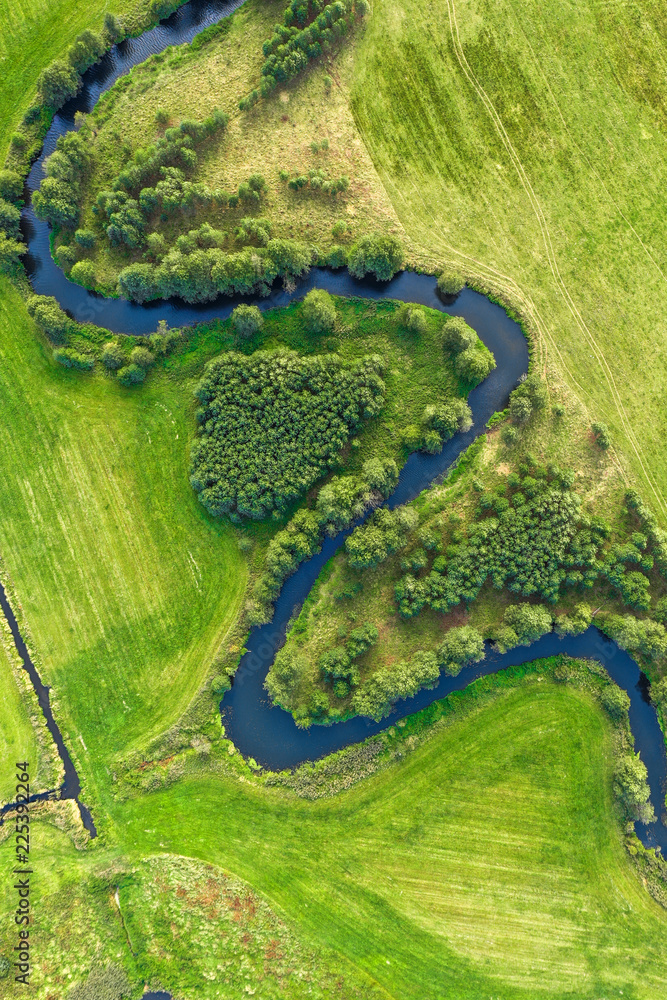 Aerial view on winding river in green field