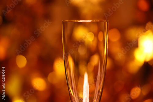 Fotobehang Alcohol Empty champagne glass gold bokeh studio