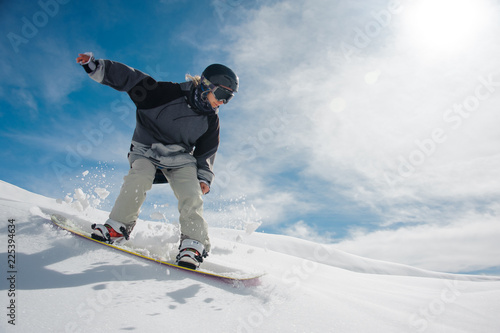 Young female snowboarder running down the mountain slope