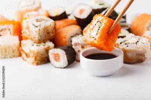 Poster Sushi bar Female hand holding wooden sticks Philadelphia roll with salmon