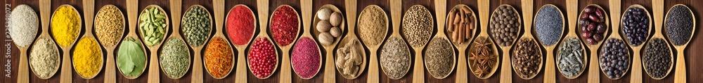 przyprawy w drewniane łyżki na czarny stół. zestaw przypraw i ziół do ozdabiania nagłówków lub paczek z jedzeniem.
