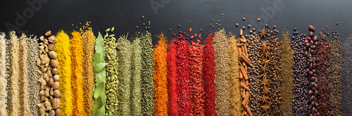 Fototapeta Colorful collection spices and herbs on background black table. Mediterranean condiments for decorating packing with food. obraz