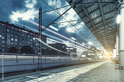 Fotografering  Highspeed train departs from the station platform at evening time