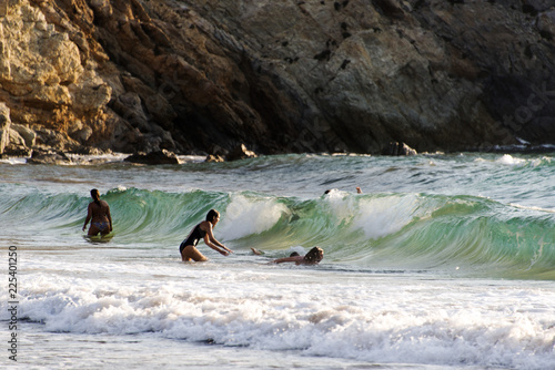 Foto op Aluminium Cathedral Cove People palying, swimming in the waves in the island of Patmos, Greece in summer time