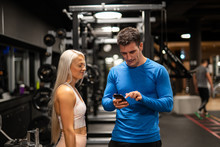 Man And Woman Using Smartphone In Gym