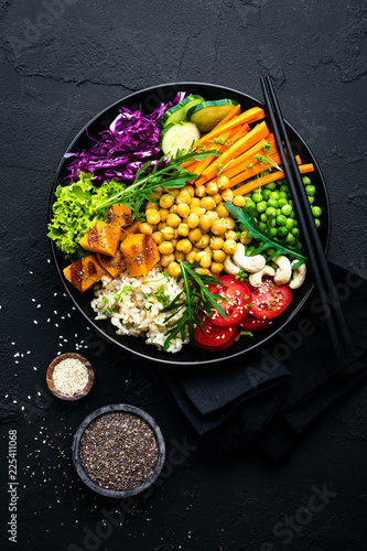 Garden Poster Personal Bowl dish with brown rice, cucumber, tomato, green peas, red cabbage, chickpea, fresh lettuce salad and cashew nuts. Healthy balanced eating