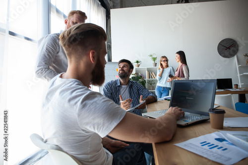 62f125601b5 Creative office. Young modern colleagues in smart casual wear working while  spending time in the