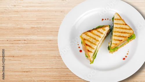 Grilled halves of sandwiches on white plate