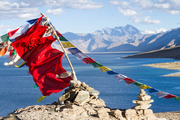 Buddhist prayer flags on the wind against the blue lake, mountains and sky