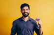 canvas print picture - Portrait of a smiling bearded man showing credit card isolated over yellow background