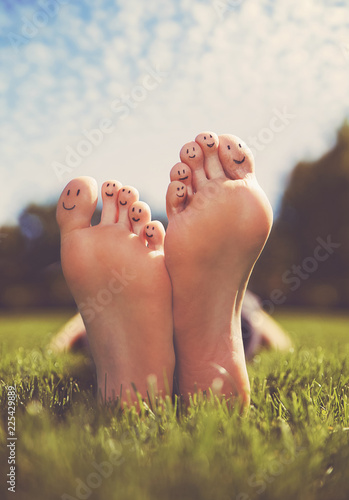 Foto shallow DOF on a man with his smiley face painted feet crossed in a park on a ho