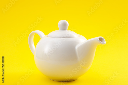 White ceramic teapot, china pot or tea kettle isolated on yellow background