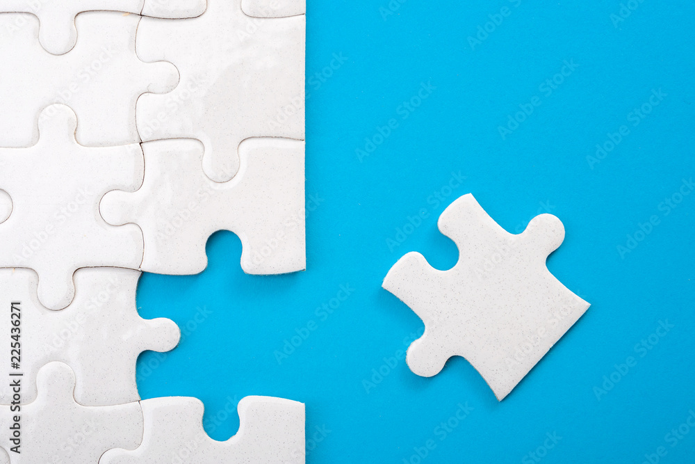 Fototapety, obrazy: Teamwork, completing the final task and finding the solution concept with the missing piece of a jigsaw puzzle next to unfinished board isolated on blue with copy space