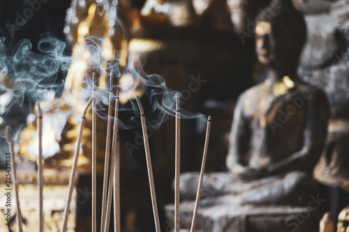 Incense sticks are burning in front of an altar with Buddha figurines, selective focus