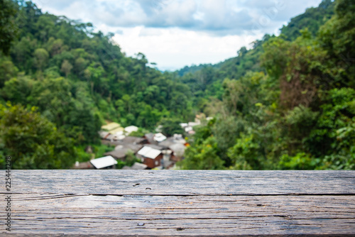 Wood table with Green Forest on the blurred background.