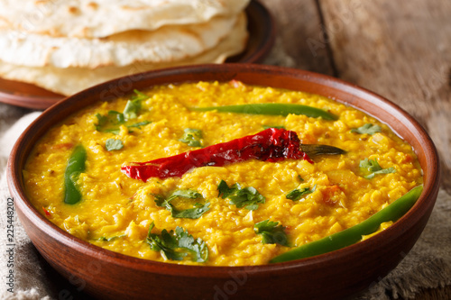 Daal Curry traditional Indian food made of yellow lentil with spices and herbs close up in a bowl. Horizontal