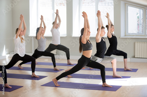 Poster Ecole de Yoga Group of young sporty people practicing yoga lesson, doing Warrior one exercise, Virabhadrasana I pose, working out, indoor, students training in club, studio. Well-being concept