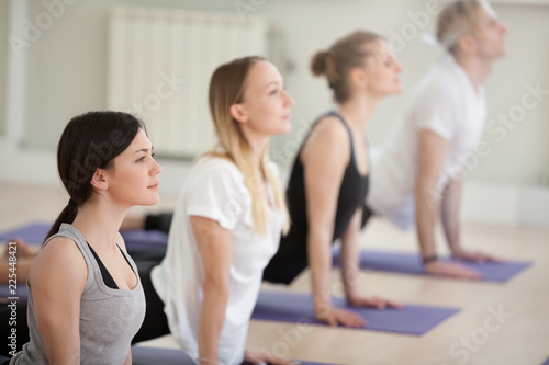 Group of young sporty people practicing yoga lesson, doing upward facing dog exercise, Urdhva mukha shvanasana pose, working out indoor, students training in sport club, studio. Well-being concept