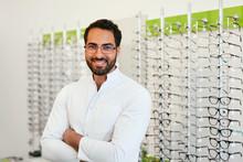 Optician Man Near Showcase With Eyeglasses At Glasses Shop