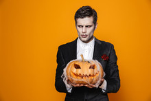 Displeased Zombie Man Holding Pumpkin And Looking Aside
