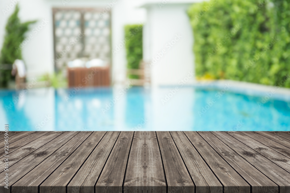 Fototapeta Empty wooden table in front with blurred background of swimming pool