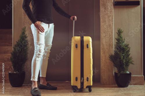 Plakat Nie do poznania człowiek z torba podróżna czekając na windę w korytarzu.