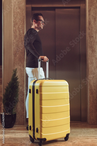 Plakat Człowiek z walizką czekając na windę w holu.