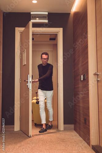 Plakat Mężczyzna z torba podróżna wchodzić do w pokoju hotelowym.
