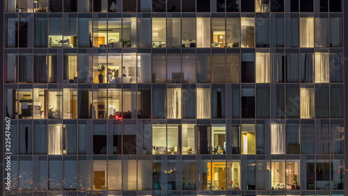 Canvas Print Windows of the multi-storey building of glass and steel lighting inside and movi