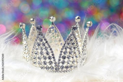 Valokuva Eine silberne Krone auf weißem Fell mit buntem Hintergrund Haarschmuck