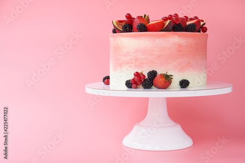 Fényképezés  Cake with whipped pink cream, decorated with fresh strawberries, blackberry, figs and red currant on pink background