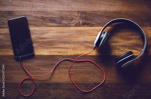 Foto  Object technology,Digital smartphone and white headset on wooden background