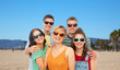 friendship, summer and people concept - group of happy smiling friends in sunglasses hugging over venice beach background in california