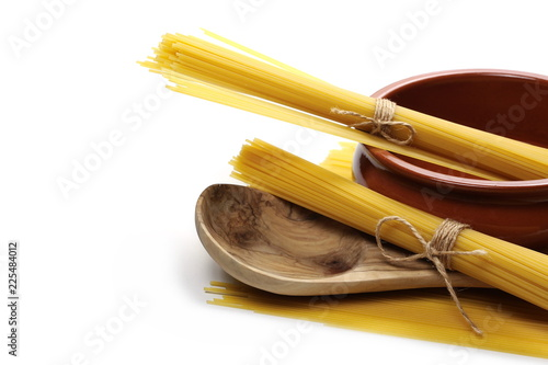 Fotografia  Spaghetti, yellow pasta, clay pot and wooden spoon isolated on white background