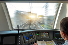 Train Driver At The Controls Cab Of Speed Passenger Train, View Of The Railway Bridge With The Effect Of Speed Motion Blur.