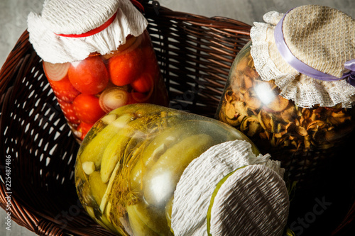 Fotografía  closeup glass jars with homemade canned vegetables lie in basket