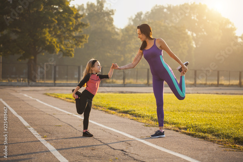 Mom and daughter on the morning sports training do a warm-up. Healthy lifestyle